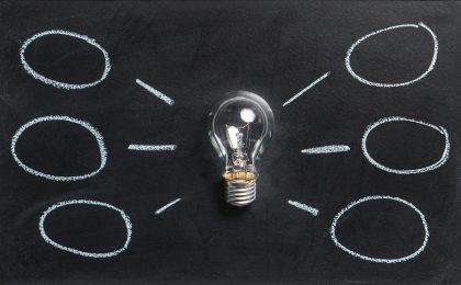 idea bubbles on blackboard with light bulb in centre