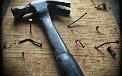 hammer with nails on wooden block